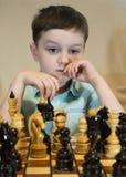 Junge, der Schach spielt Stockbild