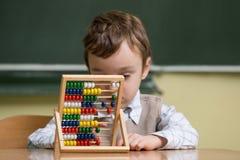 Junge in der Schule, die mit Abakus arbeitet Stockbild