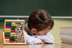 Junge in der Schule, die mit Abakus arbeitet Lizenzfreie Stockbilder