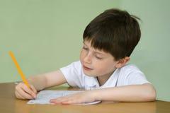 Junge, der Schulearbeit erledigt Stockbild