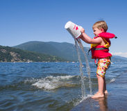 Junge, der am See spielt Lizenzfreies Stockbild