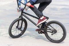 Junge, der sein BMX-Fahrrad nahe Rampen reitet Lizenzfreie Stockfotos