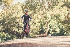 Junge, der sein Fahrrad auf eine Sandbahn fährt lizenzfreies stockfoto