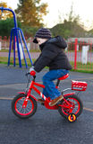 Junge, der sein Fahrrad durch einen Park reitet stockfoto