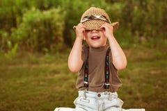 Junge, der sein Gesicht mit seinem Hut versteckt Lizenzfreie Stockbilder