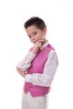 Junge, der sein Kinn in seiner ersten heiligen Kommunion auf Weiß hält Lizenzfreie Stockfotos