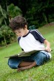 Junge, der sein Lesebuch im Freien genießt Lizenzfreies Stockfoto