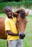 Junge, der sein Pferd umarmt Stockfotos