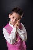 Junge, der sein Rosenbeet in seiner ersten heiligen Kommunion hält Stockbilder