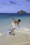 Junge, der sein skimboard reitet Stockbilder