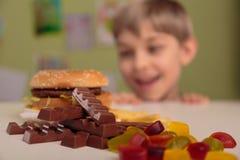 Junge, der sein ungesundes Mittagessen genießt Lizenzfreie Stockbilder