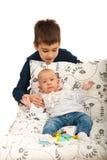 Junge, der seine kleine Schwester sich interessiert Stockbilder
