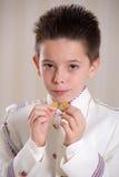 Junge, der seine Medaillen in seiner ersten heiligen Kommunion zeigt Stockfotografie