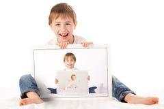 Junge, der seine Schätzchenfotos anhält Stockfoto