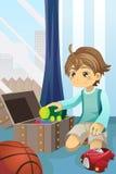 Junge, der seine Spielwaren aufräumt Stockfotos