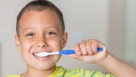 Junge, der seine Zähne und Lächeln bürstet Stockbild