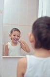 Junge, der seine Zähne vor Spiegel putzt Stockbild