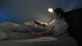 Junge, der in seinem Bett am Abend unter Verwendung seiner digitalen Tablette stillsteht stock video footage