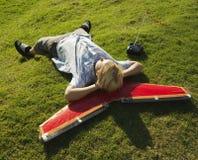 Junge, der seinen Kopf auf Flugzeug legt und stillsteht. Lizenzfreie Stockfotografie