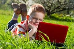 Junge, der seinen Laptop im Freien im Park verwendet Lizenzfreie Stockfotos