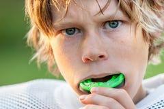 Junge, der in seinen Mundschutz sich setzt Stockbilder