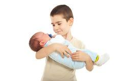 Junge, der seinen neugeborenen Bruder anhält Lizenzfreie Stockfotos