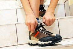 Junge, der seinen Schuh bindet stockbild