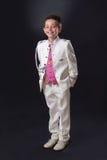Junge, der in seiner ersten heiligen Kommunion steht und lächelt Lizenzfreie Stockfotografie