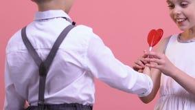 Junge, der seiner Freundin Herz-förmigen Lutscher, romantisches Geschenk, Liebe gibt stock video