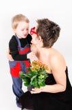 Junge, der seiner Mutter eine Blume gibt Stockbild