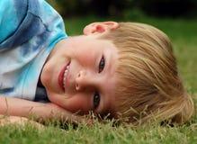 Junge, der sich im Gras hinlegt Stockfotografie