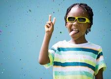 Junge in der Sonnenbrille, die Friedenszeichen gegen blauen Hintergrund und Konfettis macht Lizenzfreie Stockbilder
