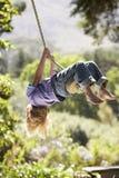 Junge, der Spaß auf Seil-Schwingen hat Stockfotografie