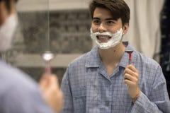 Junge, der Spaß beim Rasieren des Gesichtes hat stockbilder