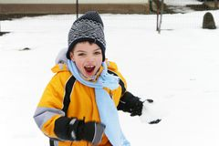 Junge, der Spaß in einem Schneeballkampf lacht und hat stockfotografie