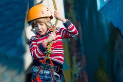 Junge, der Spaß hat und am Erlebnispark spielt, Seile hält und hölzerne Treppe klettert stockfotos