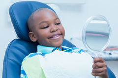 Junge, der Spiegel im Zahnarztstuhl betrachtet Stockbilder