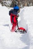 Junge, der spielt, um Schnee zu löschen Stockfoto