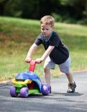 Junge, der Spielzeugfahrrad drückt Stockfoto