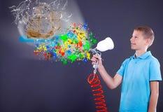 Junge, der Spray hält und abstrakte bunte Design wi malt Stockfotografie