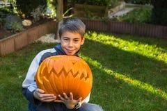 Junge, der Steckfassung-Olaterne vom großen Kürbis hält Lizenzfreie Stockfotos