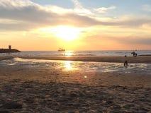 Junge, der am Strand bei Sonnenuntergang spielt Lizenzfreie Stockfotografie