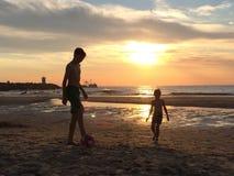 Junge, der am Strand bei Sonnenuntergang spielt Stockbilder