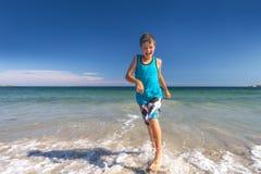 Junge, der am Strand läuft Lizenzfreie Stockfotografie