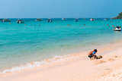 Junge, der am Strand in Thailand spielt Lizenzfreie Stockfotos