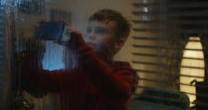Junge, der Sturm durch Fenster filmt stock footage