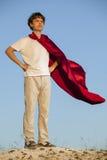 Junge, der Superhelden auf dem Himmelhintergrund, Jugendsuperhelden spielt Stockfotos