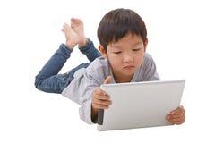 Junge, der Tablette beim Lügen auf dem Boden verwendet stockbild