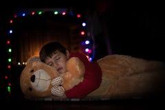 Junge, der Teddybären schläft und umarmt Lizenzfreie Stockbilder