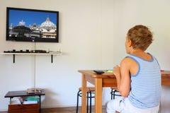 Junge, der am Tisch und an überwachendem Fernsehapparat sitzt Lizenzfreie Stockbilder